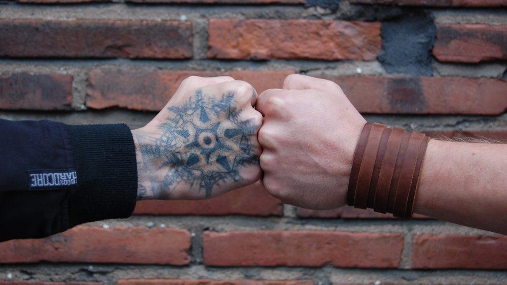 Kuvassa kaksi ihmistä lyö nyrkissä olevia käsiä yhteen.