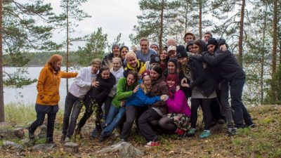 Ryhmä ihmisiä metsässä toisiinsa nojaillen.