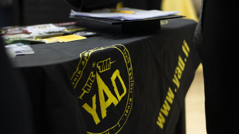 Kuva mustasta pöytäliinasta, jossa YAD:n logo.