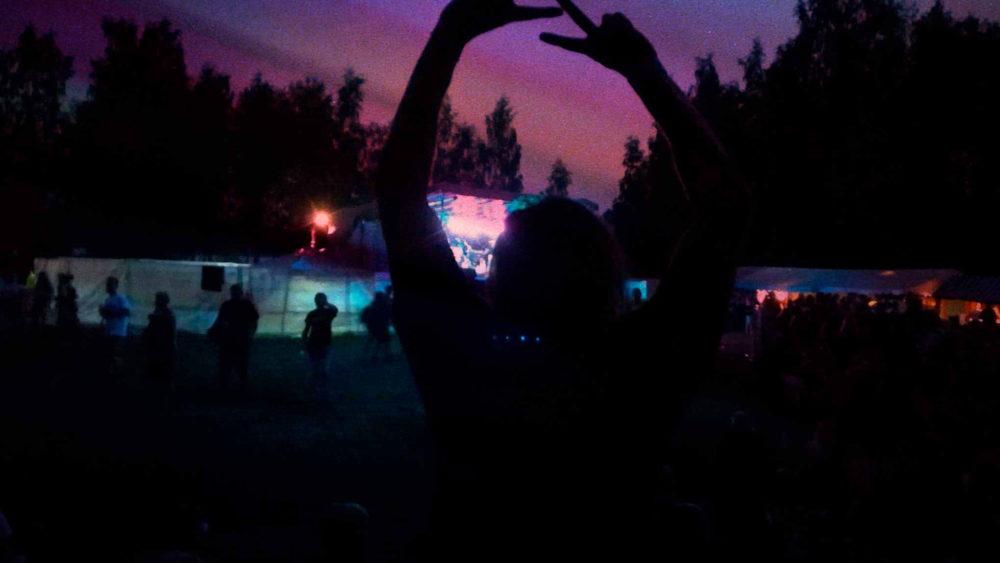 Hämärä kuva, jossa värikäs taivas auringonlaskun aikaan. Etualalla näkyy ihmisen siluetti kädet ylhäällä, kummankin käden etu- ja keskisormi pystyssä.